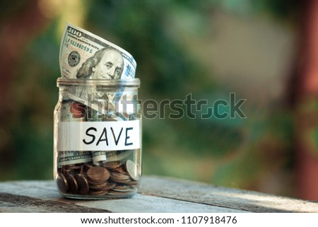 Glass jars with dollars and text save.
