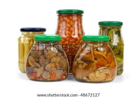 Glass jars with marinated vegetables and mushrooms isolated on the white background