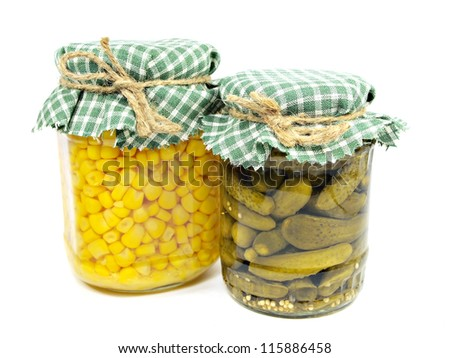 Glass jars with pickled cucumbers and canned sweet corn on a white background