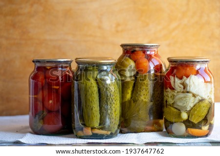 Glass jars with pickled cucumbers (pickles), pickled tomatoes and cabbage. Jars of various pickled vegetables. Canned food in a rustic composition. Сток-фото ©