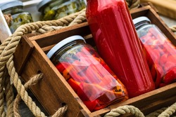 Glass jars with pickled red bell peppers and bottles with tomatoes sauce isolated in a rustic composition. Jars with variety of pickled vegetables preserved food concept.