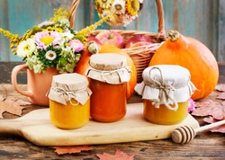 Glass jars with pumpkin jam and honey. Fresh vegetables on the table.