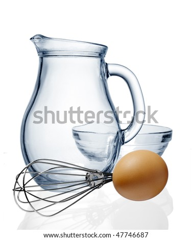 Glass jug and egg on a white background