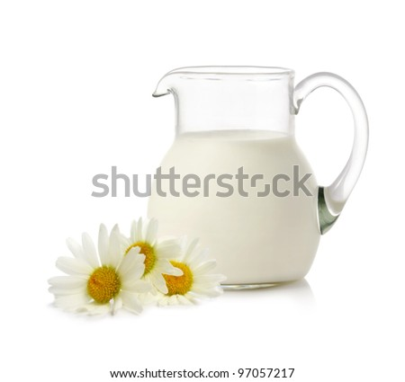Glass jug with milk and chamomiles on white background