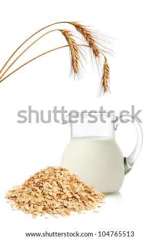 Glass jug with milk, wheat ears and cereal flakes on white background