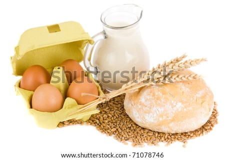 Glass jug with milk, wheat seeds, eggs and roll on white background