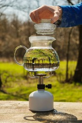 Glass kettle filled with water and heated on a camping gas burner. The lid is removed from the kettle to add tea.