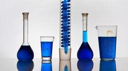 Glass laboratory test tubes and flasks with blue liquid stand on a mirror table in a row. White background.
