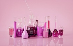 Glass laboratory tubes and flasks of pink liquid are placed in a row on a mirrored table in the laboratory. Lilac background.