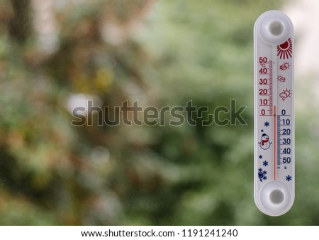 Glass liquid thermometer (with plastic frame), calibrated in degrees Celsius and attached to the outside of the window, blurred background consisting of autumn trees, close-up, free space on the left
