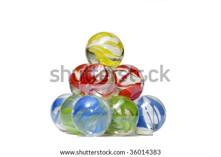 Glass marble balls pyramid macro shot over white background
