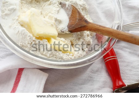 Glass mixing bowl with wooden spoon, butter and flour with pastry blender alongside on dish cloth