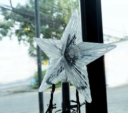 Glass Moravian Star and Tiny Christmas Lights in A House, Sign for Christmas Celebration.