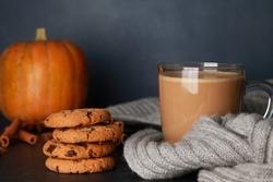 Glass mug of coffee with milk, grey woolen scarf, cookies, spices, orange pumpkins in black table against dark blue wall background. Spicy latte, thanksgiving, coffee shop menu, closeup