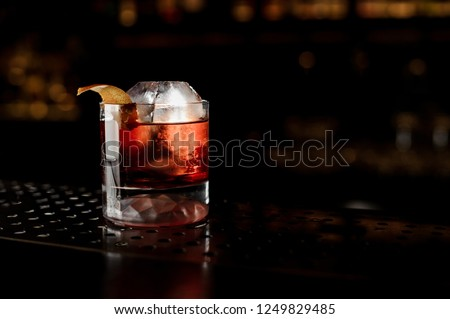 Glass of a Boulevardier cocktail with big ice cube and orange zest on the steel bar counter on the dark blurred background