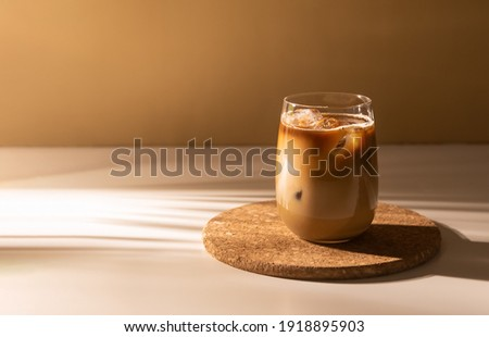 Glass of a iced coffee with cream milk. Cold brew coffee drink with ice. Early morning sun light. Copy space.