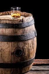 Glass of aged brandy or whiskey on the rocks and old oak barrel