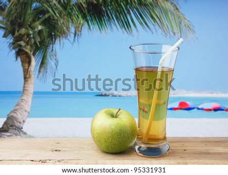 Glass of apple juice on a beach table
