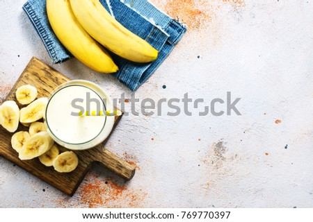 Glass of banana milk shake on the wooden table #769770397
