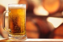 Glass of beer against barrels