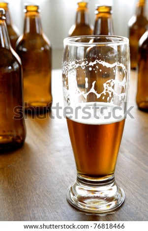 Glass of beer and bottles on table