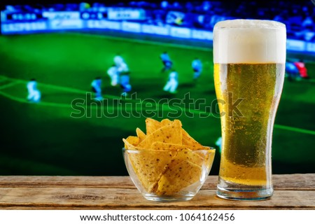 Glass of beer and snack on a football game TV background