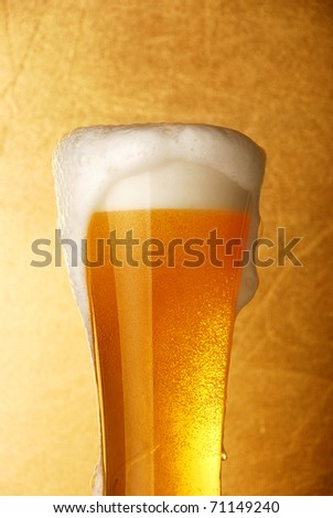 Glass of beer close-up over yellow background