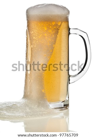 Glass of beer close up with froth isolated on white