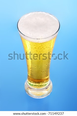 Glass of beer close-up with froth over blue background