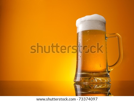 Glass of beer close-up with froth over orange background
