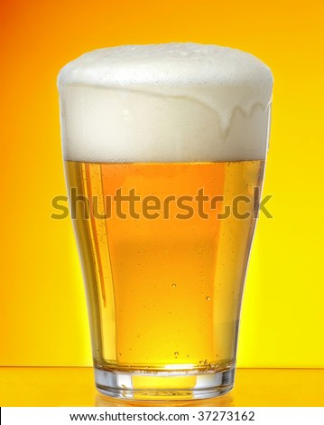 Glass of beer closeup with froth over yellow background
