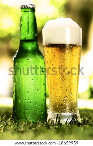 Glass of beer in front with foam, drops and chips of ice and a green bottle of beer in the back out of focus, both over the grass with an intense shinny light