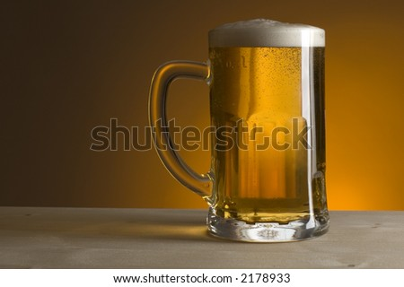 glass of beer on orange background close up