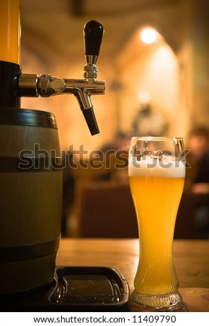 Glass of beer on pub yellow background