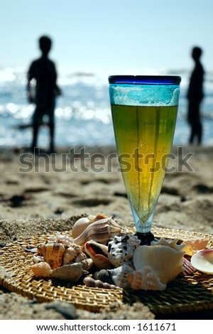 Glass of beer on the beach with a family in the background
