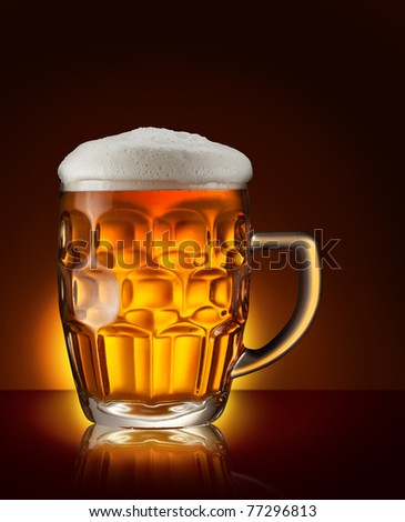 Glass of beer on the dark brown background