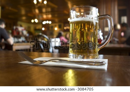 glass of beer on the table in pub close up