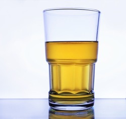 Glass of beer on white back-lit background, lager beer, wet glass, cold alcohol drinks. Closeup cold glass of beer on white background. Refreshment. Cool alcohol drinks. Thick glass, pint of beer