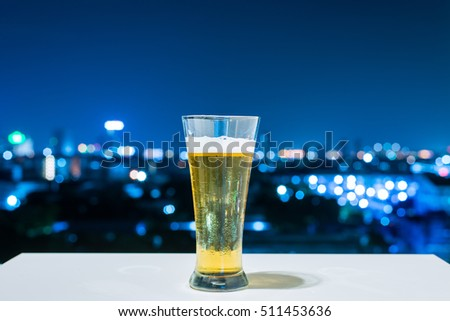 Glass of beer on white table of City at night background.