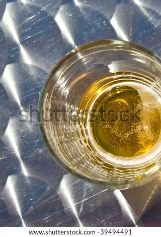 Glass of beer with edges outside center seen from above on metallic table