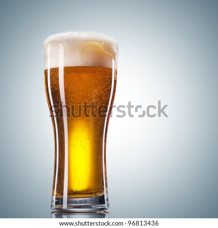 Glass of beer with froth close up on white background