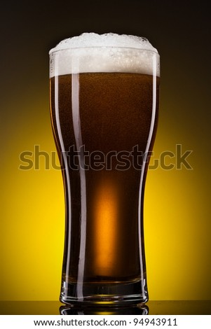 Glass of beer with froth close up over yellow gradient background