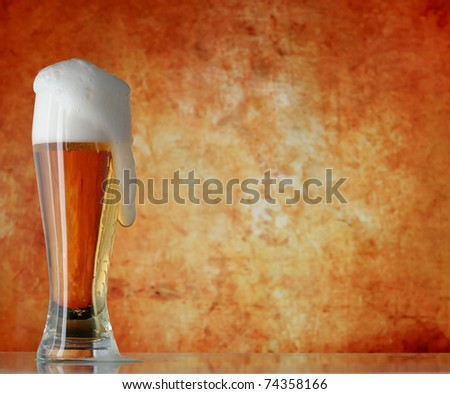Glass of beer with froth over yellow background
