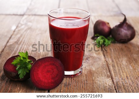 Glass of beet juice with beets on wooden table close up