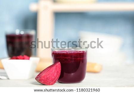 Glass of beet smoothie on table against blurred background