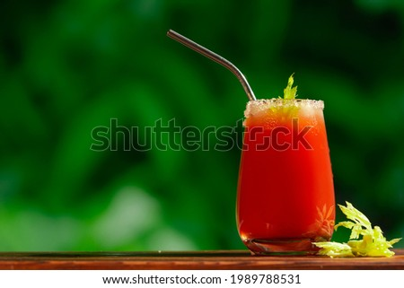 Glass of Bloody Mary cocktail rimmed salt decorated celery. Alcohol tomato juice and vodka cocktail on summer background. Copy space. Stock fotó ©