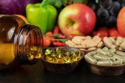 Glass of bottle with food supplement on fruits and vegetables background . Health concept.