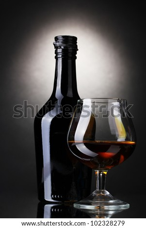 Glass of brandy and bottle on gray background