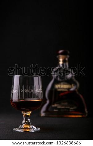 glass of brandy on a black background vertical photo. glass of brandy on the background of a bottle of brandy #1326638666