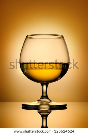 Glass of brandy on a gold background